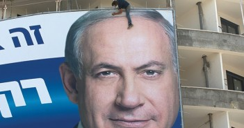 "Workers hang on a building a giant campaign poster showing Israeli Prime Minister and Likud party's candidate running for general elections Benjamin Netanyahu on March 8, 2015 in the costal Israeli city of Tel Aviv. Tens of thousands of people rallied in Tel Aviv on March 7, 2015 against Netanyahu and called for ""change"", 10 days ahead of a general election.  AFP PHOTO / MENAHEM KAHANA / AFP PHOTO / MENAHEM KAHANA"