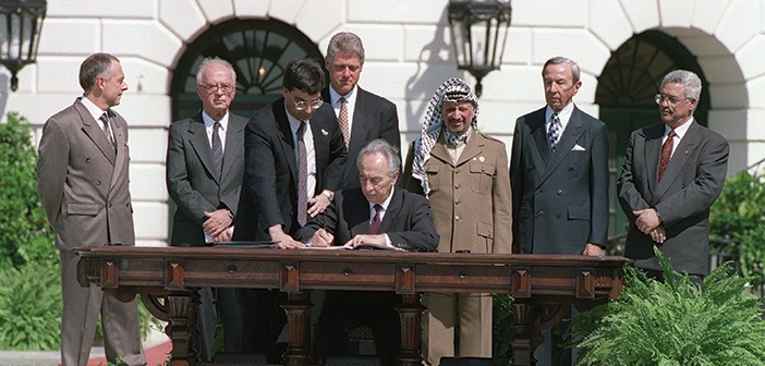 Israeli Foreign Minister Shimon Peres (C) signs the historic Israel-PLO Oslo Accords on Palestinian autonomy in the occupied territories on September 13, 1993 in a ceremony at the White House in Washington, D.C. as (from L to R) Russian Foreign Minister Andrei Kozyrev, Israeli Prime Minister Yitzhak Rabin, unidentified aide, US President Bill Clinton, PLO Chairman Yasser Arafat, US Secretary of State Warren Christopher, and PLO political director Mahmoud Abbas look on. / AFP PHOTO / J. DAVID AKE