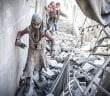 ALEPPO, SYRIA - NOVEMBER 17: Civilians run around the debris of damaged buildings after the war crafts belonging to the Assad Regime's and Russian forces' airstrikes over residential areas at Firdevs neighborhood in Aleppo, Syria on November 17, 2016. It is reported that at least 94 people killed and 150 others wounded due to airstrikes those staged within last 48 hours. (Photo by Jawad al Rifai/Anadolu Agency/Getty Images)